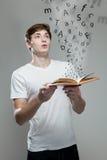 拿着与字母表信件的年轻人一本书 免版税库存图片
