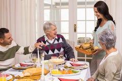 拿着与家庭的妇女火鸡烘烤在圣诞节 免版税库存照片