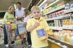 拿着与家庭的男孩橙汁在超级市场 免版税库存图片