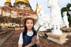 拿着与尊敬的亚裔女孩游人一朵莲花或在Wa祈祷 免版税库存照片