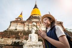 拿着与尊敬的亚裔女孩游人一朵莲花或在Wa祈祷 库存照片