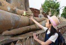 拿着与尊敬的亚裔女孩游人一朵莲花或祈祷 免版税库存照片