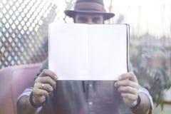 拿着与开放空白纸的可爱的行家博客作者笔记薄在手上,当花费时间在咖啡馆时大阳台上  空间 库存照片