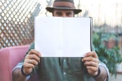 拿着与开放空白纸的行家男性作家笔记薄在手上,当花费时间在咖啡馆时大阳台上  空间为 库存图片