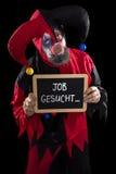 拿着与德国文本工作的小丑板岩哀伤地要,概念 免版税图库摄影