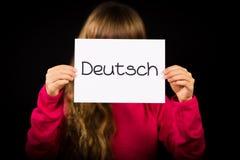 拿着与德国词德意志-德语的孩子标志用英语 免版税库存照片