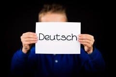 拿着与德国词德意志-德语的孩子标志用英语 库存图片