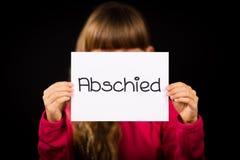 拿着与德国词Abschied的孩子标志-再见 免版税库存图片