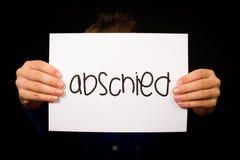 拿着与德国词Abschied的孩子标志-再见 库存图片