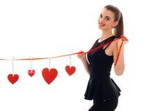 拿着与心脏和微笑的黑礼服的逗人喜爱的女孩一条红色丝带 库存照片