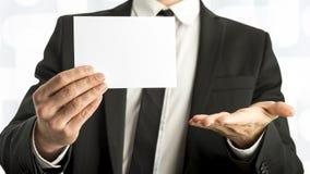 拿着与拷贝空间的商人白色卡片 免版税库存照片
