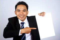 拿着与指向的英俊的亚洲商人姿态的一个白纸 免版税库存图片