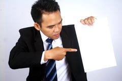 拿着与指向的英俊的亚洲商人的照片图象姿态的一个白纸 免版税库存照片