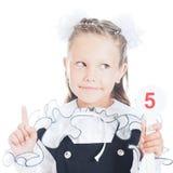 拿着与数字的女小学生一个标志在他的手上 库存照片