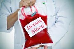 拿着与文本的医生血液袋子捐赠血液 免版税库存图片
