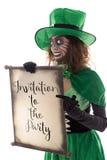 拿着与文本邀请t的滑稽的绿色gobling的女孩一个纸卷 图库摄影