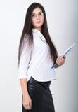 拿着与文件的一块白色女衬衫、黑皮革裙子和玻璃的一名年轻人相当亭亭玉立的亚裔妇女一个文件夹 免版税库存照片