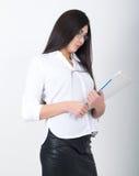 拿着与文件的一块白色女衬衫、黑皮革裙子和玻璃的一名年轻人相当亭亭玉立的亚裔妇女一个文件夹 图库摄影