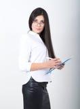 拿着与文件的一块白色女衬衫、黑皮革裙子和玻璃的一名年轻人相当亭亭玉立的亚裔妇女一个文件夹 库存图片