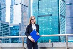 拿着与文件的女商人文件夹手中以摩天大楼为背景 库存照片