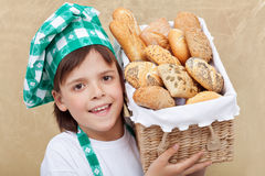 拿着与新鲜的面包店产品的愉快的面包师男孩篮子 库存图片