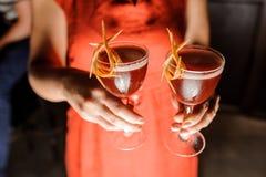 拿着与新鲜的鸡尾酒的红色礼服的妇女三块玻璃 库存图片