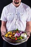 拿着与新鲜蔬菜的有胡子的人一个金属篮子 库存照片