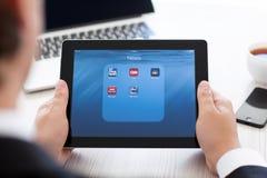 拿着与新闻app的商人iPad在屏幕上 免版税库存照片
