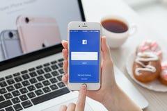 拿着与服务Facebook的妇女iPhone 6S罗斯金子 免版税库存照片