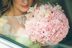拿着与桃红色花的新娘婚礼花束 库存照片