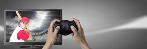 拿着与棒球运动员的手赌博控制器在电视上 免版税图库摄影