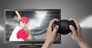 拿着与棒球运动员的手赌博控制器在电视上 图库摄影