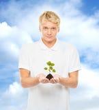 拿着与植物的年轻和英俊的十几岁的男孩土壤 免版税库存照片