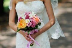 拿着与橙色白色和桃红色花的新娘婚礼花束 免版税库存照片
