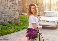 拿着与步行沿着向下街道的生动的束的妇女秸杆袋子淡紫色花 免版税图库摄影