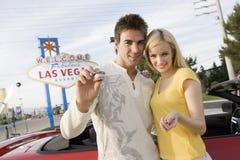 拿着与汽车的夫妇赌博娱乐场芯片在背景中 免版税图库摄影