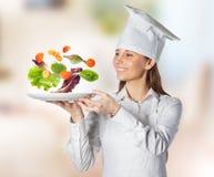 拿着与浮动的蔬菜的愉快的厨师妇女一个盘在厨房 库存照片