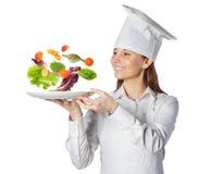 拿着与浮动的蔬菜的愉快的厨师妇女一个盘 免版税图库摄影