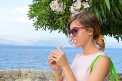 拿着与海边的深色的女孩一束白花在背景中 免版税图库摄影