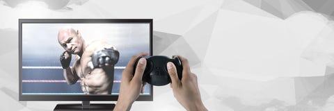 拿着与混杂的武术战斗机的手赌博控制器在电视上 库存图片