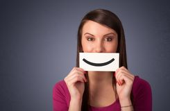 拿着与滑稽的面带笑容的愉快的俏丽的妇女卡片 免版税库存图片