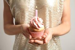 拿着与灼烧的蜡烛,特写镜头的妇女可口生日杯形蛋糕 库存图片
