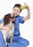 拿着与狗的女性兽医画象一个球 免版税库存照片