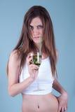 拿着与猕猴桃的年轻人适合的妇女一块玻璃编结 免版税库存图片