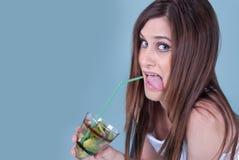拿着与猕猴桃的年轻人适合的妇女一块玻璃编结 免版税图库摄影