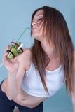 拿着与猕猴桃的年轻人适合的妇女一块玻璃编结 免版税库存照片