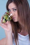 拿着与猕猴桃的年轻人适合的妇女一块玻璃编结 库存照片