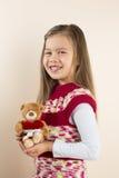 拿着与玩具重点的女孩玩具熊 免版税库存照片