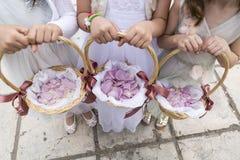 拿着与玫瑰花瓣的三个女花童篮子 库存照片