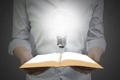 拿着与电灯泡的手开放书 免版税库存图片